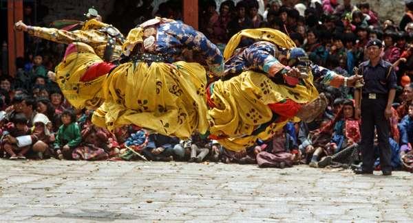 Bell dancers jumping at the Paro Tshechu, mask dance festival, in the Paro Dzong, Bhutan (photo)