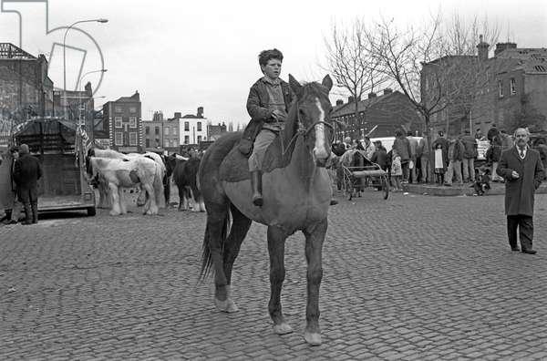 Boy riding horse for sale in Smithfield horse market, Dublin, Ireland, 90s