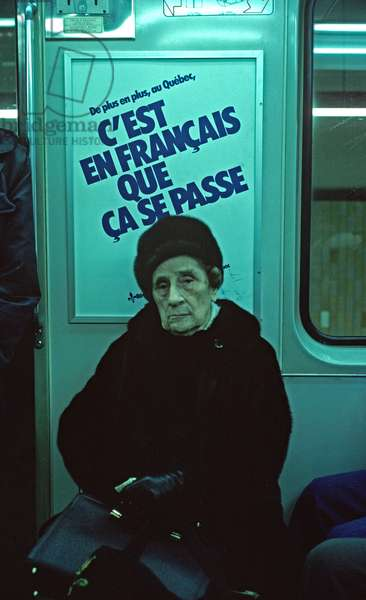 French Canadian Lady in front of poster exttolling the virtues of the French language in Montreal subway, Quebec Province, Canada (photo)