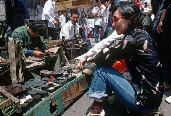 Shoe repairs in Qingdao market, Qingdao town, Shandong province, China, 1985 (photo)