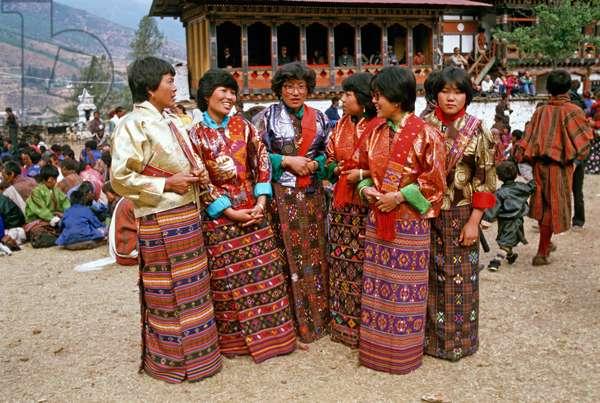 Bhutanese women in traditional costumes at the Paro Tshechu, mask dance festival, in the Paro Dzong, Bhutan (photo)