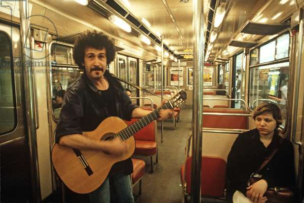 Busker playing guitar and singing in Paris Metro, France (photo)