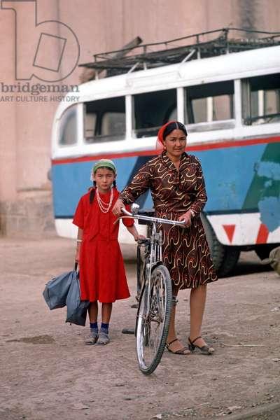 Uyghur mother and daughter pushing cycle, Turpan, Xinjiang Province, China, 1985 (photo)