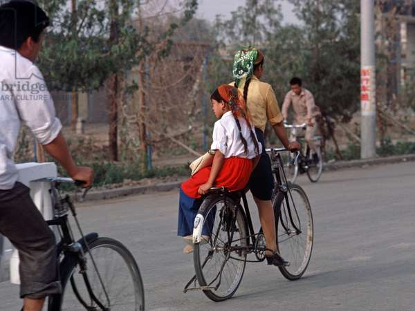 Uyghur mother and daughter cycling in Turpan, Xinjiang Province, China, 1985 (photo)