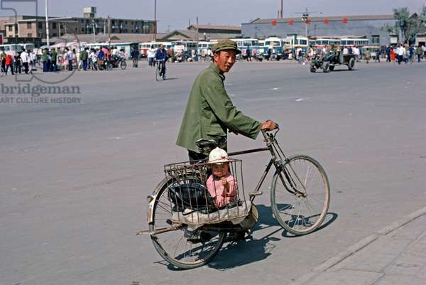 Child in bicycle carrier, Hohhot, capital of Inner Mongolia, Northern China, 1985 (photo)