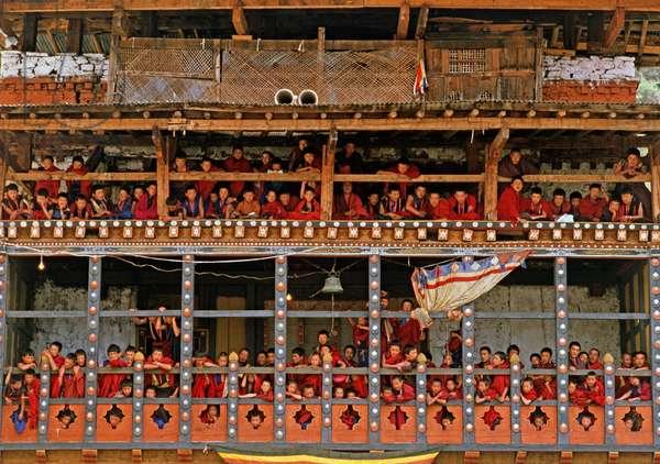 Buddhist monks watching the Paro Tshechu, mask dance festival, in the Paro Dzong, Bhutan   (photo)