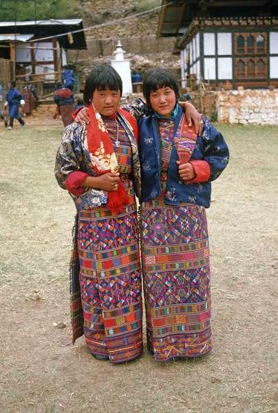 Bhutanese young women in traditional costumes at the Paro Tshechu, mask dance festival, in the Paro Dzong, Bhutan (photo)