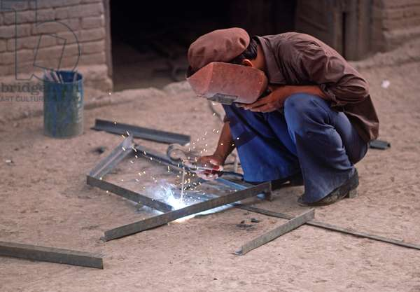 Metal workers electric soldering in Turpan, Xinjiang Province, China, 1985 (photo)