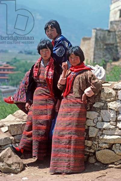 Bhutanese girls in traditional costumes at the Paro Tshechu, mask dance festival, in the Paro Dzong, Bhutan (photo)