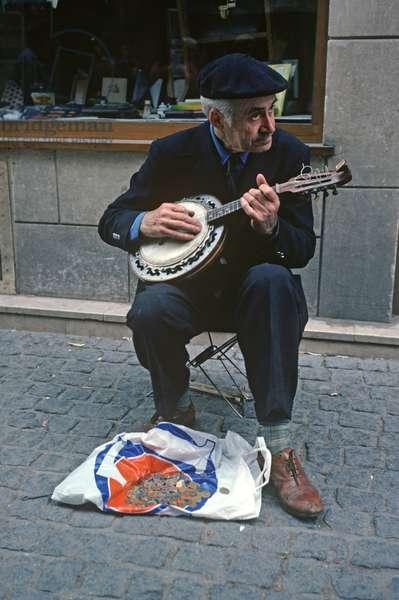 Street musician playing banjo in Paris, France (photo)
