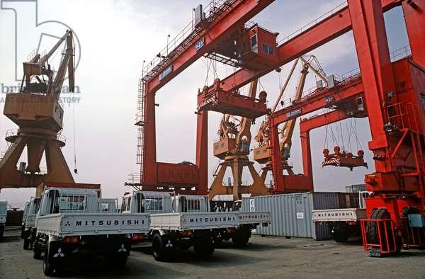 New Mitsubishi trucks being unloaded at Qingdao port, Shandong province, China, 1985 (photo)