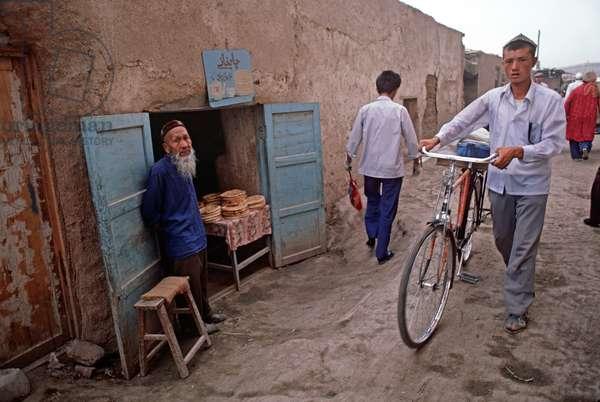 Uyghur selling flat nan bread in Turpan, Xinjiang province, China, 1985 (photo)