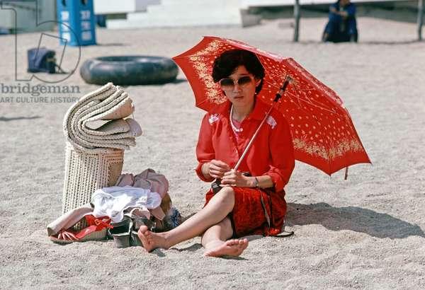 Chinese holiday makers under sun umbrellas on Qingdao beach, Sandong province, China, 1985 (photo)