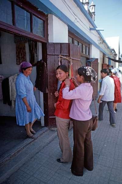 Young woman trying on jacket on Urumqi street, Xinjiang, China, 1985 (photo)