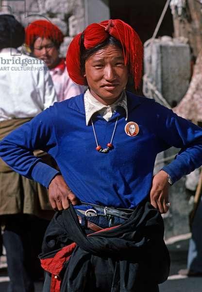Tibetan with Dalai Lama badge in Lhasa main square (photo)