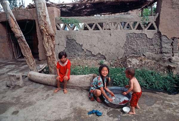 Uyghur children playing in courtyard in Turpan, Xinjiang Province, China, 1985 (photo)