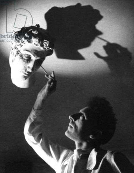 French painter Jean Cocteau painting a statue, 1936 (b/w photo)