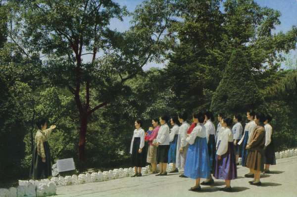A guide showing North Korean women a site near Kim Il-sung's birthplace, connected to his childhood and upbringing (colour photo)
