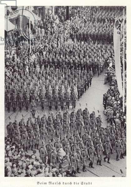 Columns of Nazi workers marching through Nuremberg, 1936 (b/w photo)