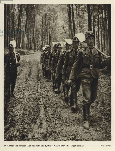 Members of the Reichsarbeitsdienst (Reich Labour Service) marching back to camp after a day's work (b/w photo)