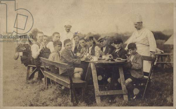 Group of boys eating at a picnic table (b/w photo)