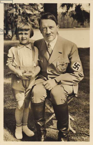 Nazi leader Adolf Hitler seated next to a child during a holiday in the Harz Mountains, Germany, c1930s