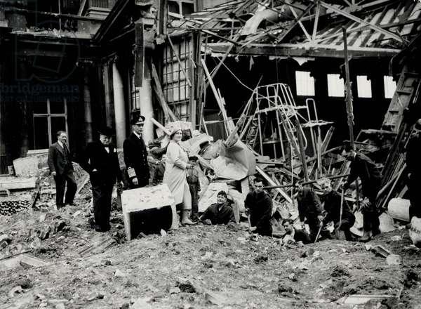 King George VI amd Queen Elizabeth, together with Winston Churchill, surveying bomb damage, presumably to Buckingham Palace (b/w photo)