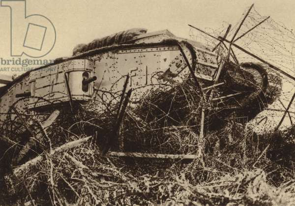 British tank attempting to break through a barbed wire obstacle, World War I, 1917-1918 (b/w photo)