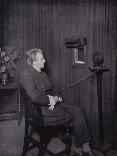 John L Baird seated before a television transmitter (b/w photo)