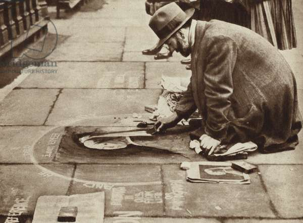 Pavement artist producing a copy of Johannes Vermeer's painting Girl with a Pearl Earring on a London street (b/w photo)