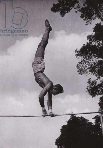 Nazi German worker peforming gymnastics exercises on the high bar (b/w photo)
