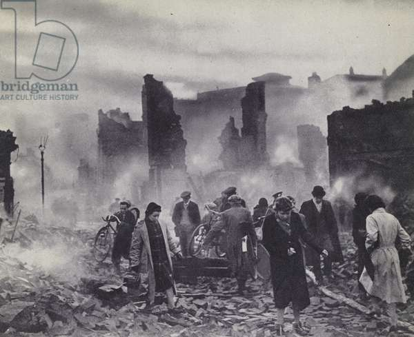 Civilians on their way to work through the ruins of their city after an air raid during the Coventry Blitz, World War II, 1940 (b/w photo)