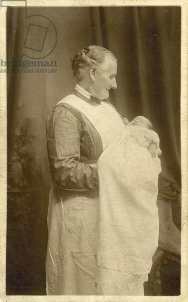 Nurse holding a baby (b/w photo)