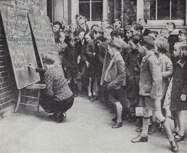Children at a communal feeding station at a London school during the Blitz, World War II, 1940 (b/w photo)