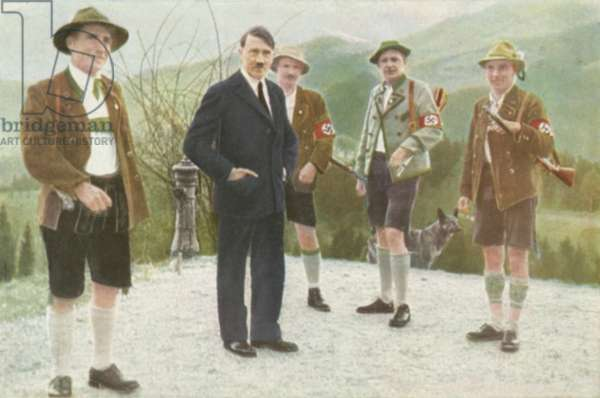 Nazi leader Adolf Hitler with a group of his Bavarian supporters wearing traditional costume (colour litho)