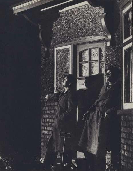 Two British air raid wardens watching the skies during the Blitz, World War II, 1940-1941 (b/w photo)