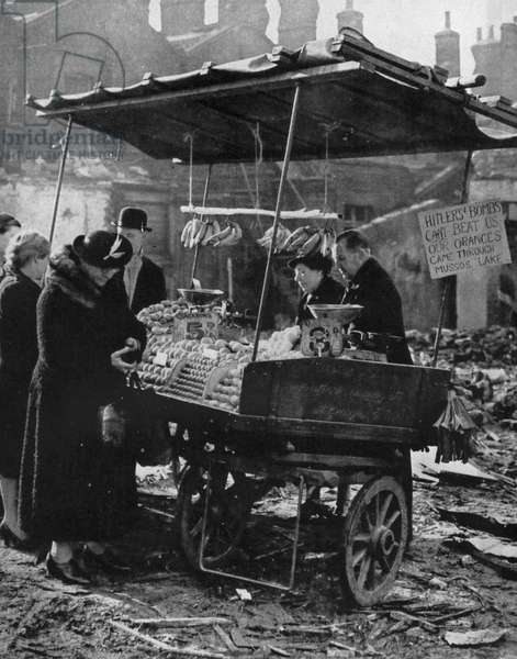 In 1940 a fruit stall open in the debris of the blitz in London (b/w photo)