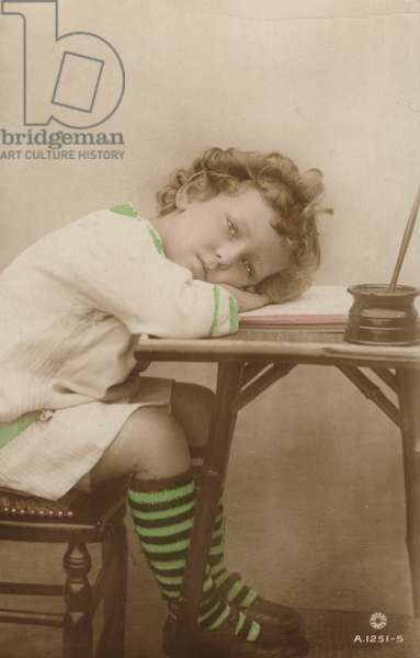 Portrait of a sleepy young child at a writing desk (coloured photo)