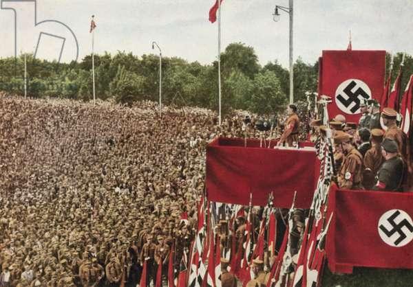 Nazi leader Adolf Hitler reviewing the parade of the SA at Dortmund, Germany, 1933 (colour photo)