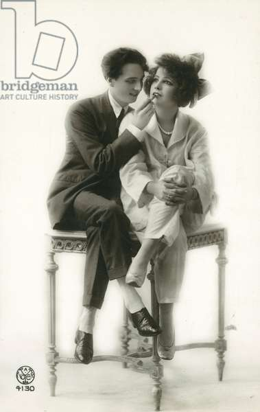 Androgynous man in suit applying lipstick to lips of girl in pyjamas (b/w photo)
