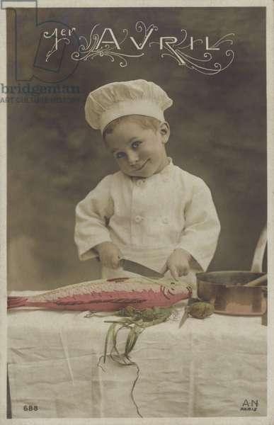 Little boy cooking a fish (colour photo)