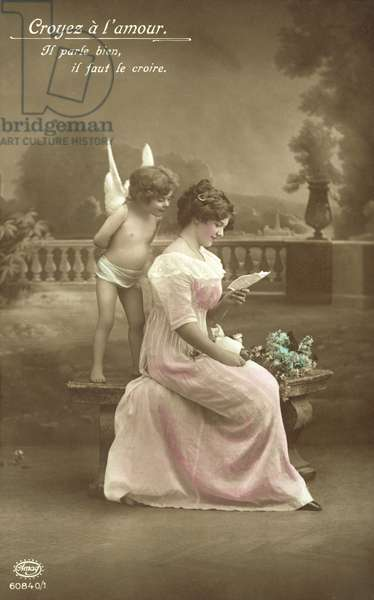 Girl reading a love letter, with Cupid looking over her shoulder (colour photo)