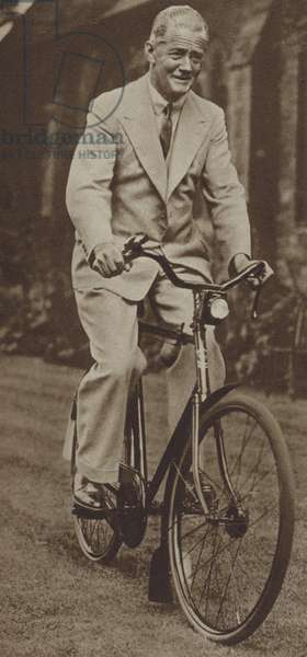 Sir William Morris, Lord Nuffield, British motor manufacturer and philanthropist, riding a bicycle (b/w photo)