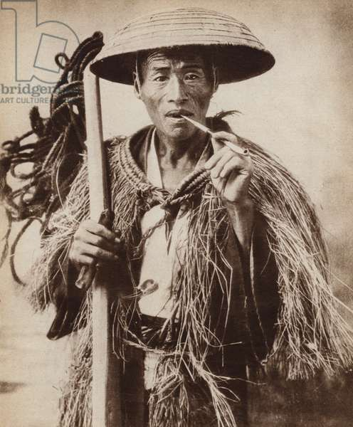 Japanese coolie (farm labourer) wearing a hat to protect him from heavy rain in the rice fields (b/w photo)