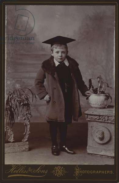 Portrait of a young boy wearing a mortar board (b/w photo)