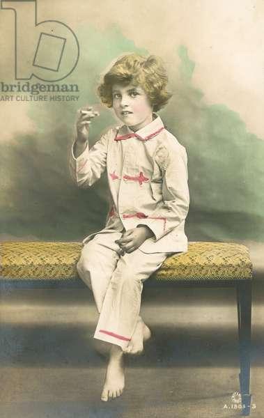 Child, wearing pyjamas, smoking (colour photo)