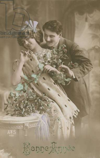 Happy New Year greetings card with romantic couple holding mistletoe, 1913 (hand-coloured photograph)