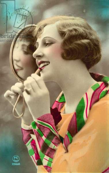 Pretty girl applying lipstick, using mirror (colour photo)
