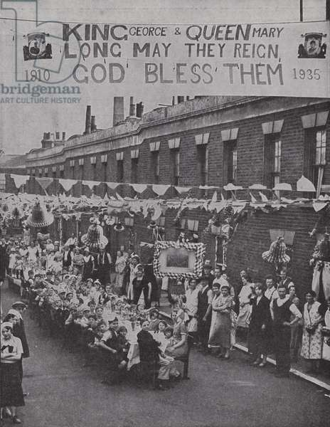 Street tea party for poor children in Palace Road in London's East End, in commemoration of the Silver Jubilee of King George V, 1935 (b/w photo)