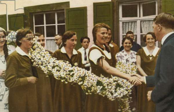 Nazi leader Adolf Hitler meeting a group of young women while visiting the Odenwald during the German election campaign of 1932 (colour photo)